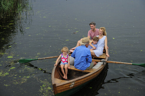 Happy family in rowing boat on lake - ECPF00152