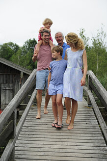 Happy family walking together on boardwalk in summer - ECPF00173