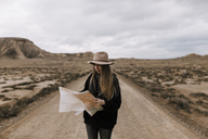 Woman with map standing on dirt road in barren landscape - JPF00300