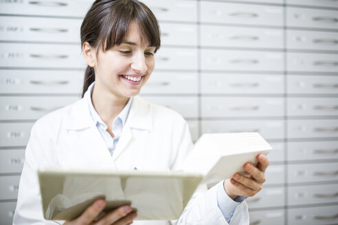 Smiling pharmacist with tablet and tablet package in pharmacy - WESTF23908
