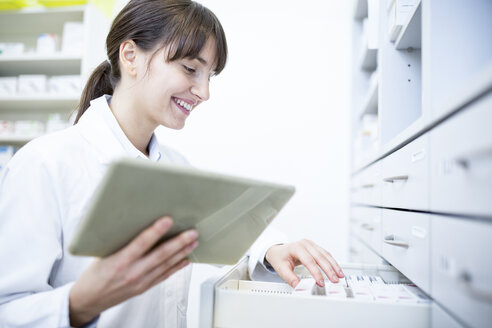 Smiling pharmacist with tablet at cabinet in pharmacy - WESTF23911