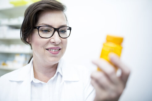 Smiling pharmacist holding pill box in pharmacy - WESTF23926
