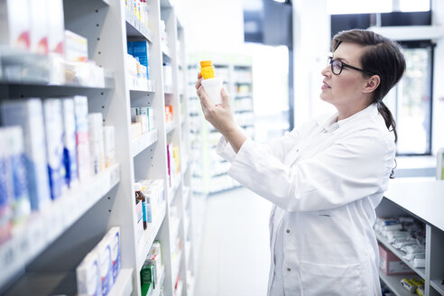 Pharmacist holding product at shelf in pharmacy - WESTF23944