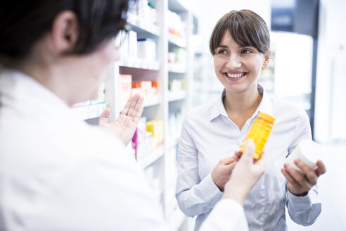 Pharmacist advising customer in pharmacy - WESTF23947