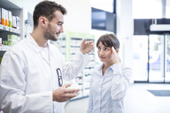 Pharmacist advising customer in pharmacy - WESTF23950