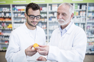 Two pharmacists examining medicine in pharmacy - WESTF23953