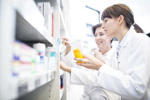 Two pharmacists with pill box at shelf in pharmacy - WESTF23956