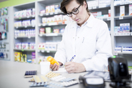 Pharmacist with medicine at counter in pharmacy - WESTF23962