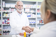 Pharmacist and customer shaking hands in pharmacy - WESTF23965