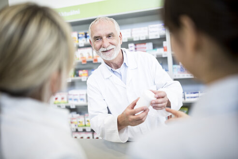 Pharmacist smiling at two women in pharmacy - WESTF23974