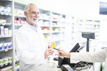 Customer paying cashless in a pharmacy - WESTF23977