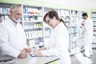 Two smiling pharmacists with clipboard at counter in pharmacy - WESTF23980