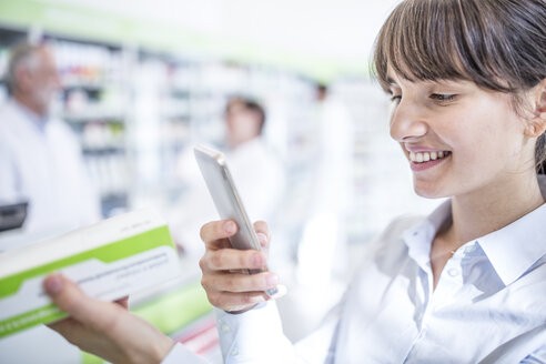 Smiling woman in pharmacy holding smartphone and medicine - WESTF23983