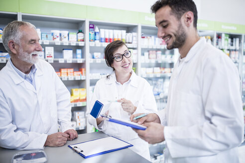 Smiling pharmacists with clipboard at counter in pharmacy - WESTF23986
