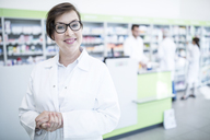 Portrait of smiling pharmacist in pharmacy with colleagues in background - WESTF23989