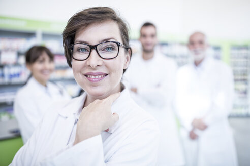 Portrait of smiling pharmacist in pharmacy with colleagues in background - WESTF23992