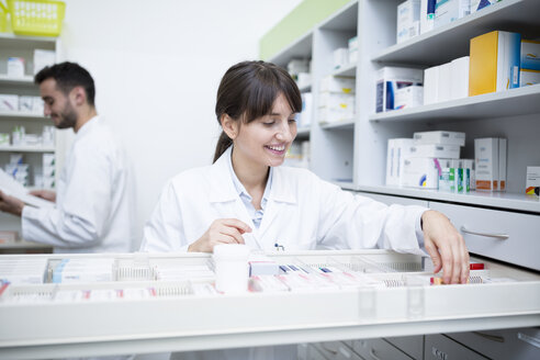 Smiling pharmacist seeking out medicine at cabinet in pharmacy - WESTF23998