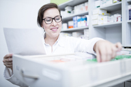 Smiling pharmacist seeking out medicine at cabinet in pharmacy - WESTF24001