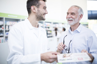 Pharmacist smiling at mature man in pharmacy - WESTF24004