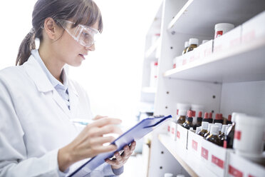 Woman holding clipboard in laboratory of a pharmacy - WESTF24013