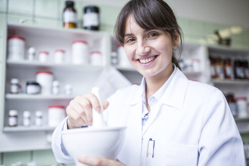 Portrait of smiling woman working in laboratory of a pharmacy - WESTF24019