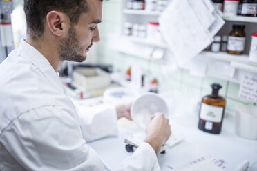 Man preparing medicine in laboratory of a pharmacy - WESTF24022