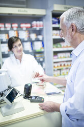Customer paying cashless in a pharmacy - WESTF24028