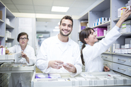 Smiling pharmacists working at cabinet in pharmacy - WESTF24031