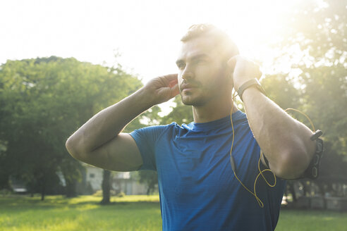 Sportive man wearing headphones, preparing for training in urban park - SBOF01113