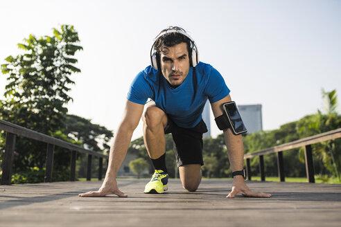 Runner training start position on street in urban park, wearing headphones - SBOF01128
