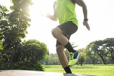 Runner training running up stairs, close up - SBOF01131