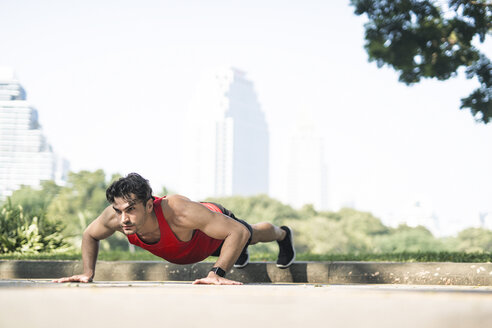 Athlete exercising push-ups in the city - SBOF01140