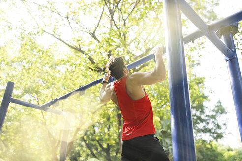 Man doing pull-ups on bars in urban park - SBOF01143