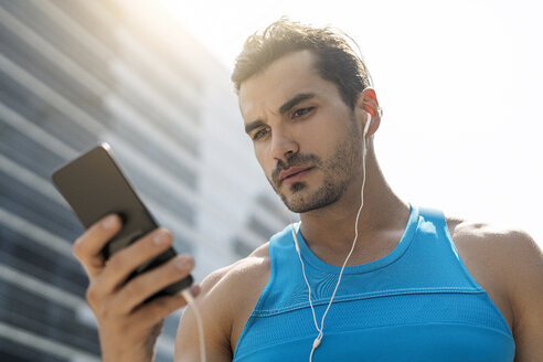 Runner wearing earphones, checking messages on his smartphone - SBOF01152