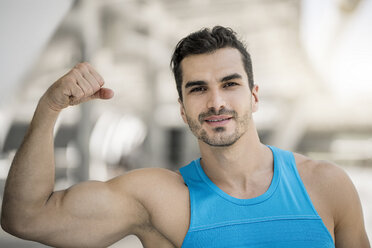 Portrait of man training in the city, flexing muscles - SBOF01155