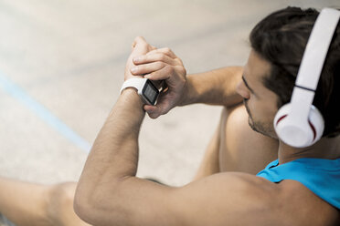 Athlete with earphones sitting on the ground, checking his smartwatch - SBOF01161