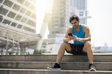 Runner wearing earphones, checking messages on his smartphone - SBOF01170