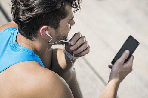 Runner wearing earphones, checking messages on his smartphone - SBOF01173