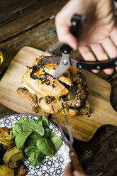 Woman jointing freshly cooked chicken - GIOF03742
