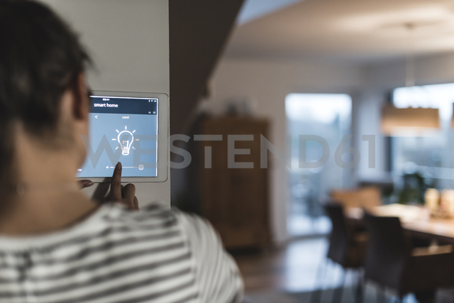 Woman using screen with smart home control functions at home - UUF12498