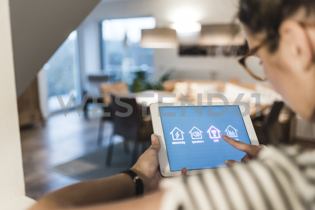 Woman using tablet with smart home control functions at home - UUF12501