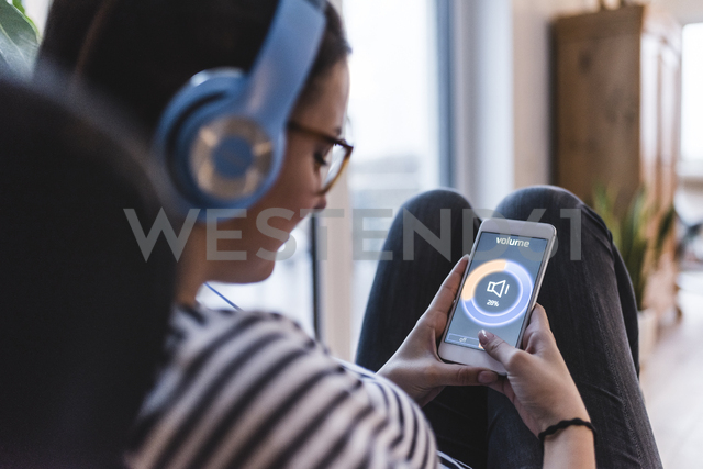Woman listening to music with headphones and smartphone at home - UUF12504