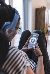 Woman listening to music with headphones and smartphone at home - UUF12507
