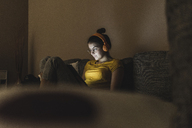 Woman with headphones listening to music on couch at home - UUF12510