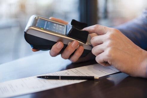 Man using credit card reader, close-up - DIGF03216