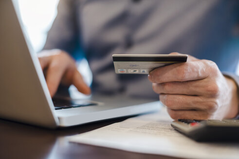 Man using laptop and holding credit card, close-up - DIGF03219