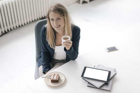 Portrait of smiling businesswoman having coffee and cake at desk in the office - JOSF02100