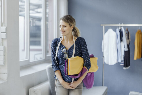 Portrait of smiling fashion designer standing in her studio - JOSF02118