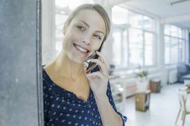 Portrait of happy young woman on the phone in a loft - JOSF02133