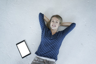 Portrait of smiling young woman lying on the floor with tablet - JOSF02142